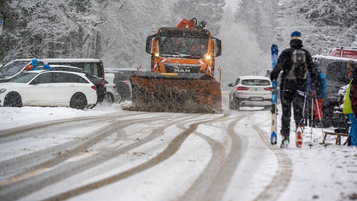 Ein Schneeräumfahrzeug fährt auf der Straße am Großen Arber an parkenden Autos vorbei.