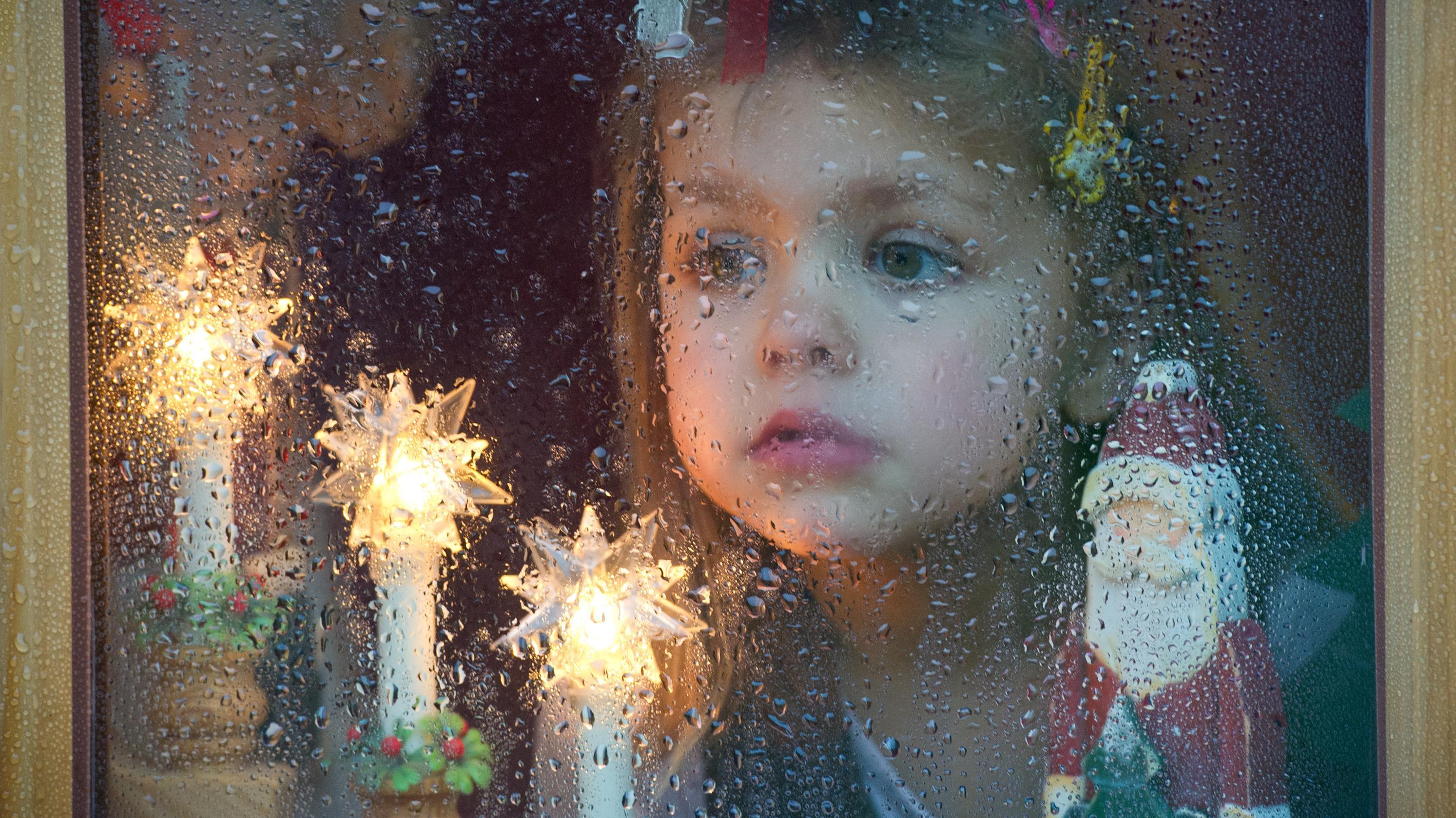Mädchen mit Weihnachtsdeko hinter einer Fensterscheibe voller Regentropfen