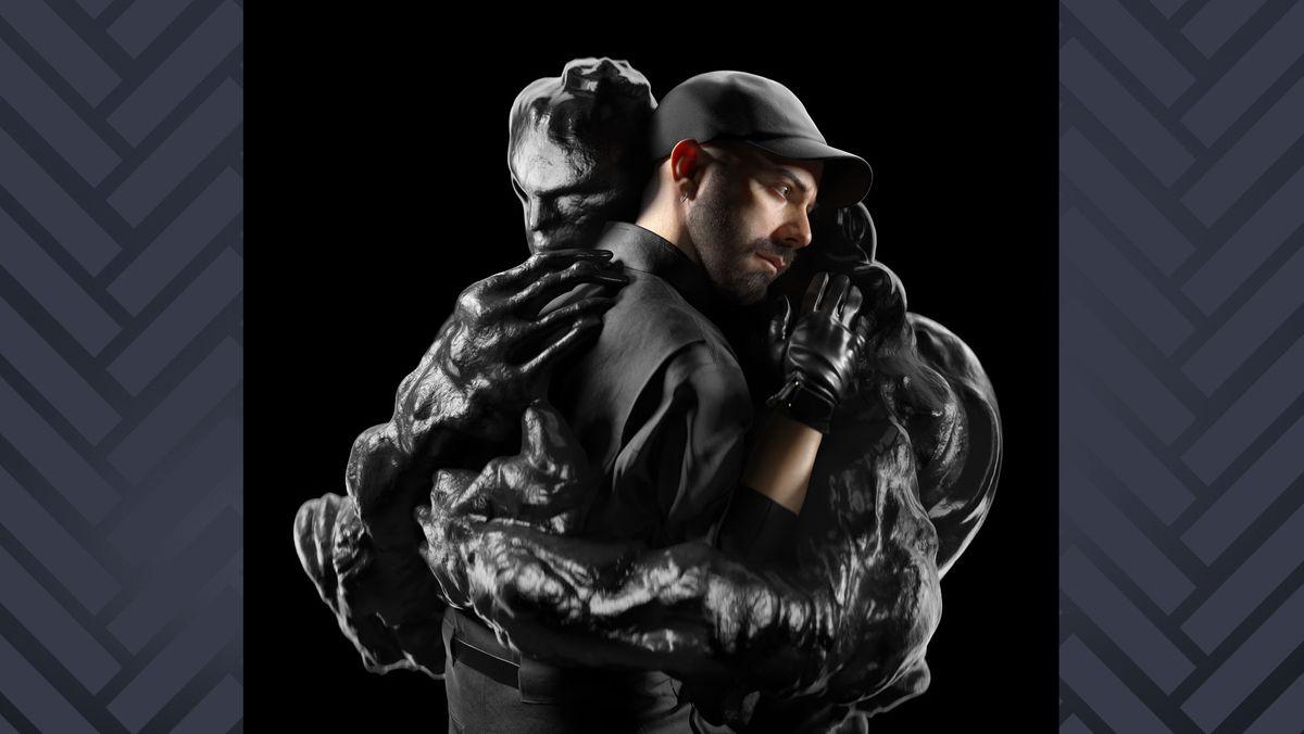 Woodkid, ganz in schwarz gekleidet und mit schwarzer Basecap umarmt eine computergenerierte, monsterhafte Gestalt, ebenfalls komplett schwarz, vor schwarzem Hintergrund.