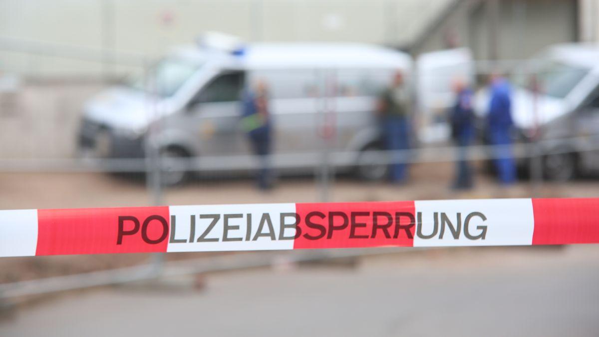 Ein rot-weißes Absperrband der Polizei hängt vor Einsatzkräften des Kampfmittelbeseitigungsdienstes