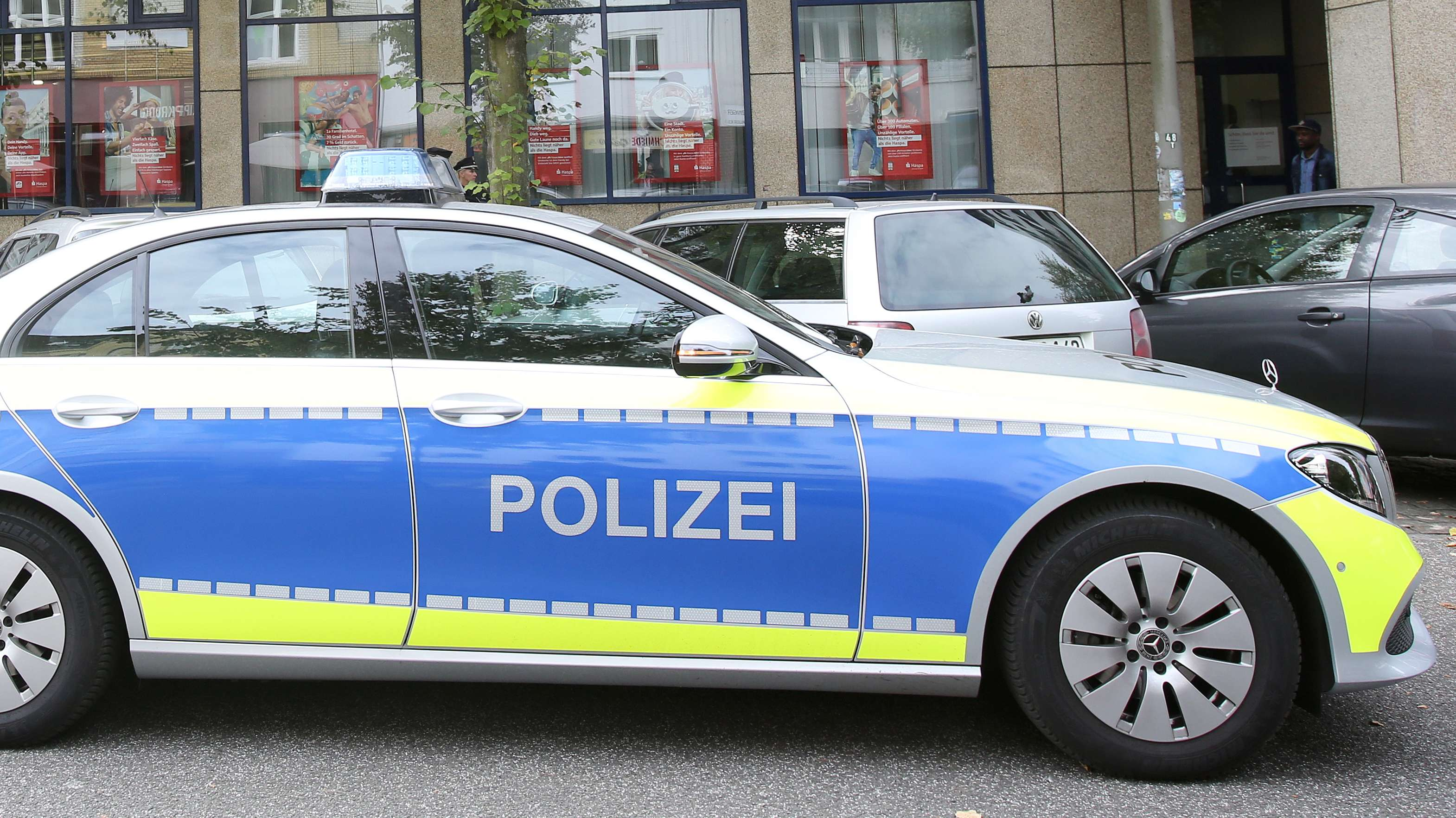 Symbolbild: Polizeiauto vor einer Sparkasse.
