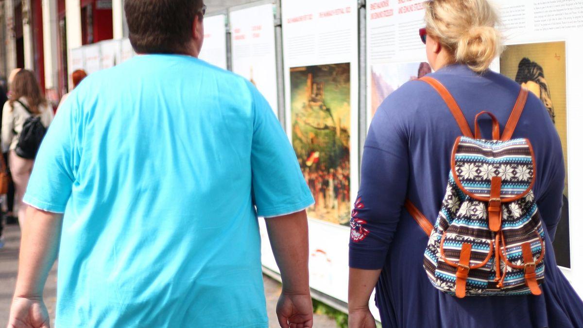 Übergewichtige Junge mit Frau beim Stadtbummel