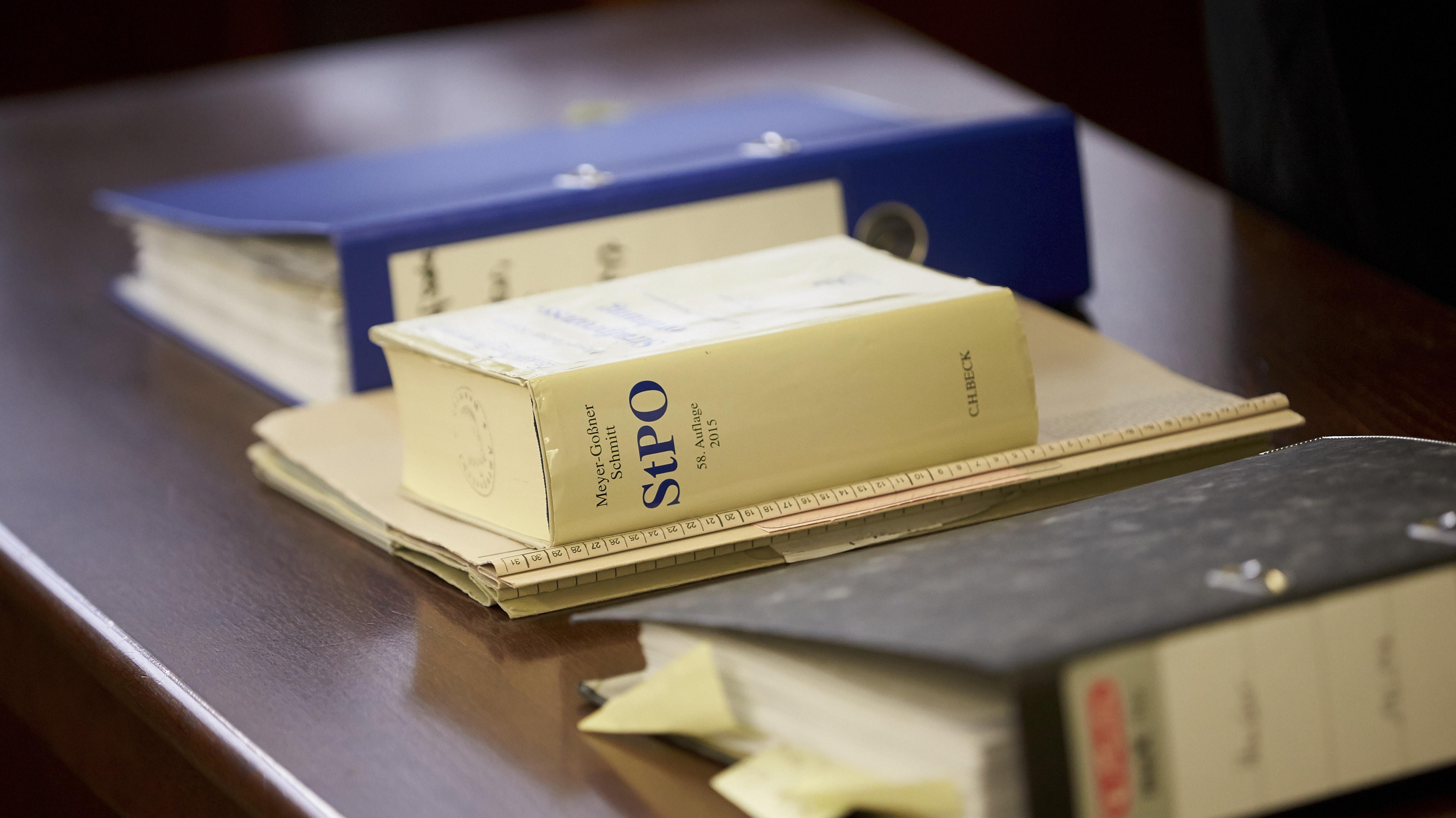 Prozess-Akten und Strafprozessordnung StPO auf Tisch in einem Gerichtssaal (Symbol)