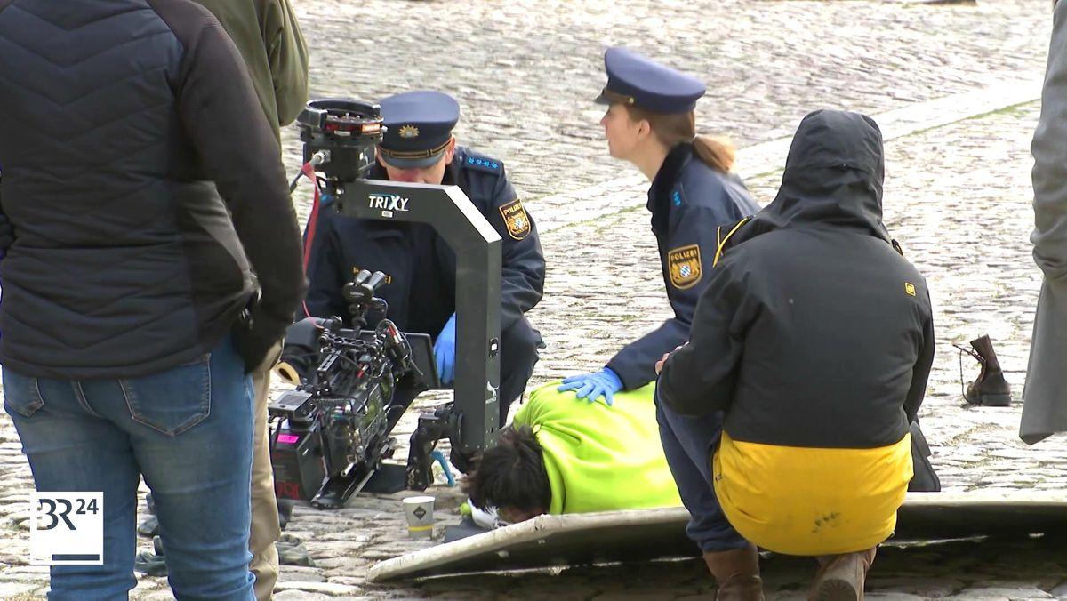 Zwei Schauspieler in Polizeiuniform knien auf dem Boden und kümmern sich um einen Verletzten, daneben eine Filmkamera.