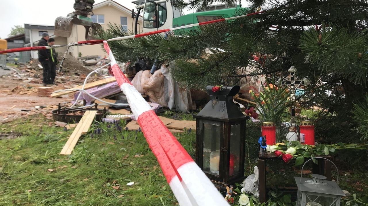 Kerzen stehen vor den Trümmern des explodierten Wohnhauses in Rettenbach.