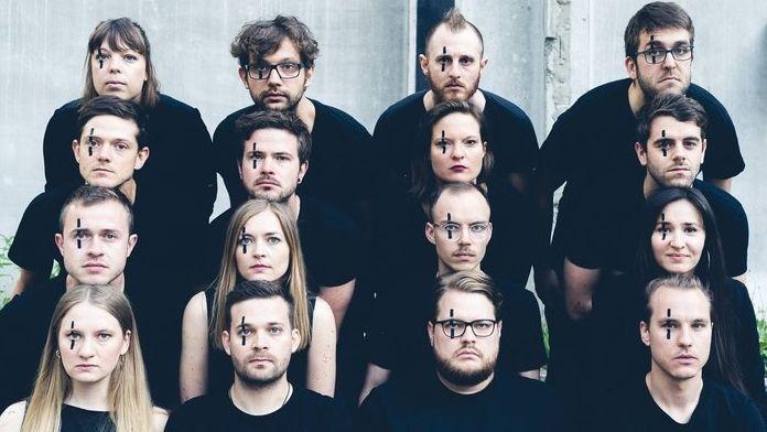 16 Musiker*innen sitzen mit schwarzem Oberteil in vier REihen hintereinander, alle haben über dem Linken Aute einen senkrechten Strich