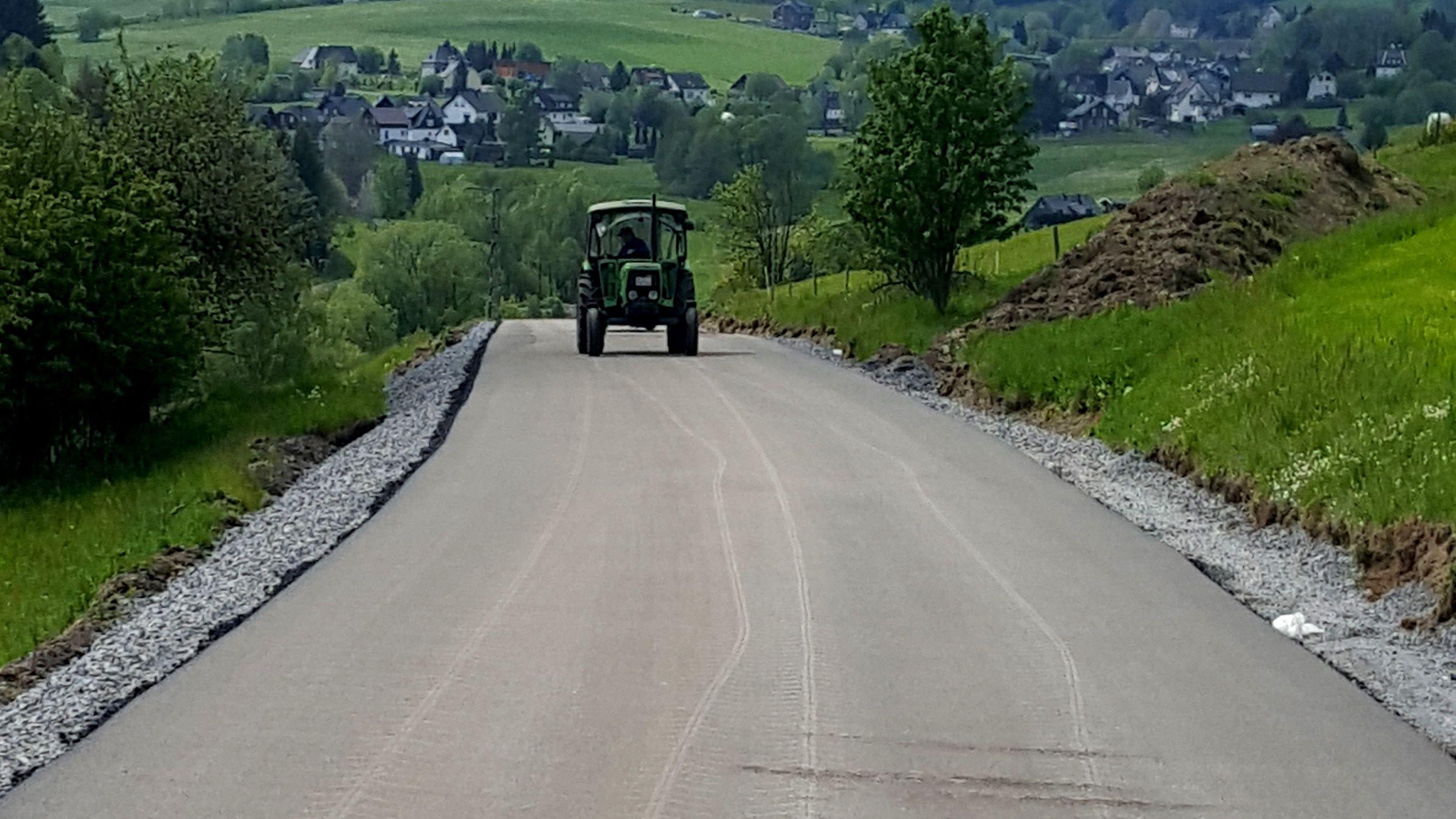 Traktor fährt über frisch geteerte Straße