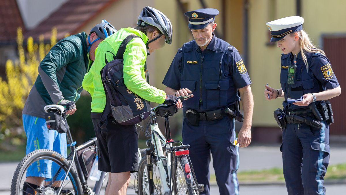 Zwei Polizisten kontrollieren zwei Fahrradfahrer.