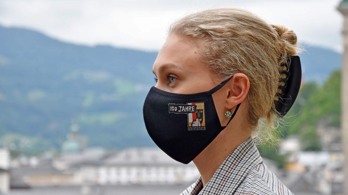 Blonde Frau mit schwarzer Stoffmaske.