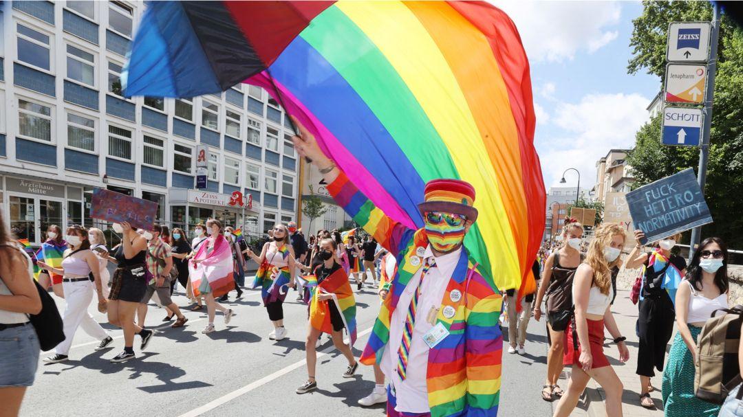 Ein Mann in regenbogenfarbener Kleidung schwingt eine passende Fahne auf einer CSD-Demo (Symbolbild).