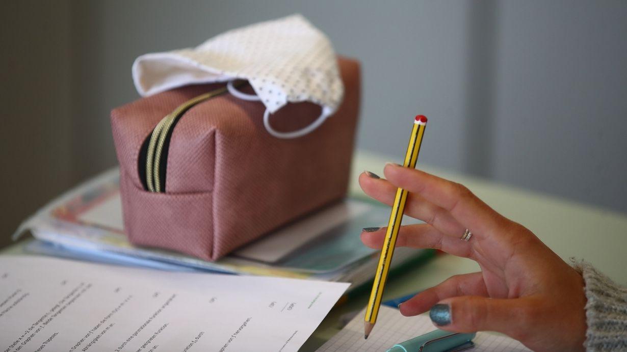 Schulutensilien und ein Mund-Nasenschutz liegen auf einem Tisch im Gymnasium Gleichense. Schulschließungen und Kontaktbeschränkungen treffen aus Expertensicht vor allem Jugendliche hart.