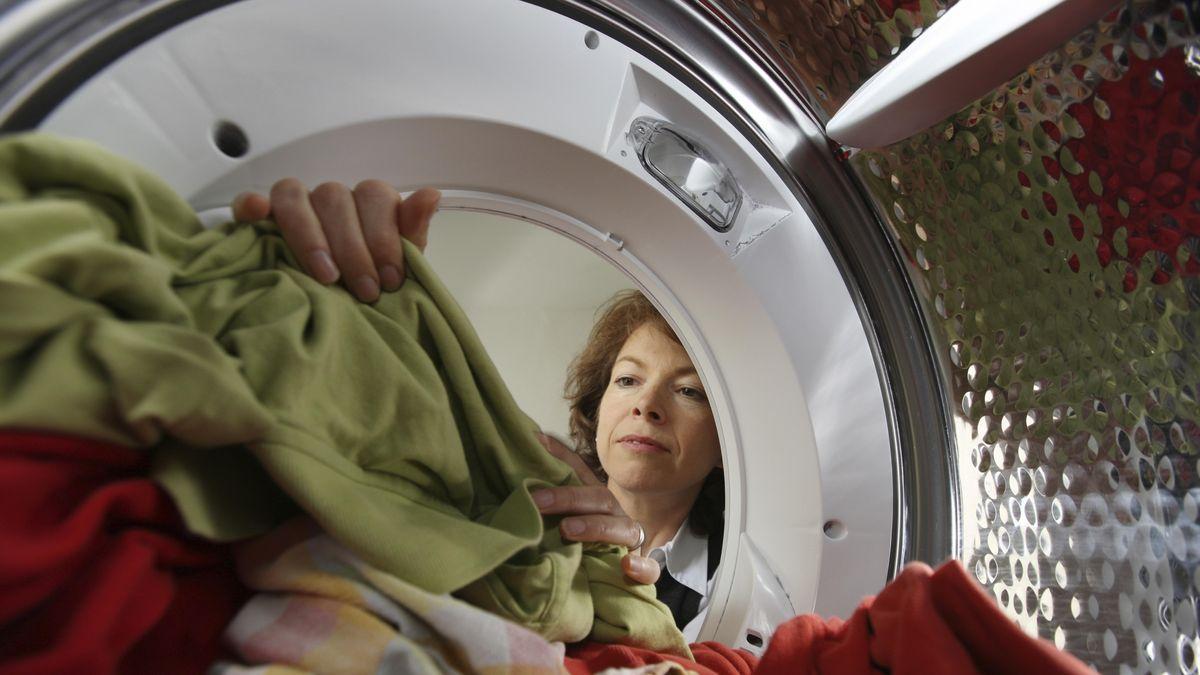 Das Bild zeigt eine Frau, die trockene Wäsche aus einem Wäschetrockner nimmt.