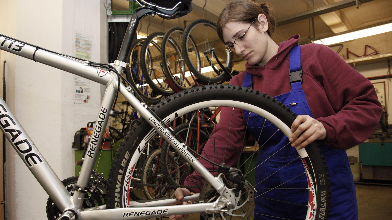 Junge Frau in der Ausbildung zur Fahrradmonteurin (Symbolbild)