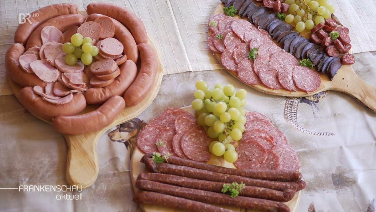 Auf drei runden Holztellern liegen Würste, aufgeschnitten und im Stück, garniert mit grünen Weintrauben.