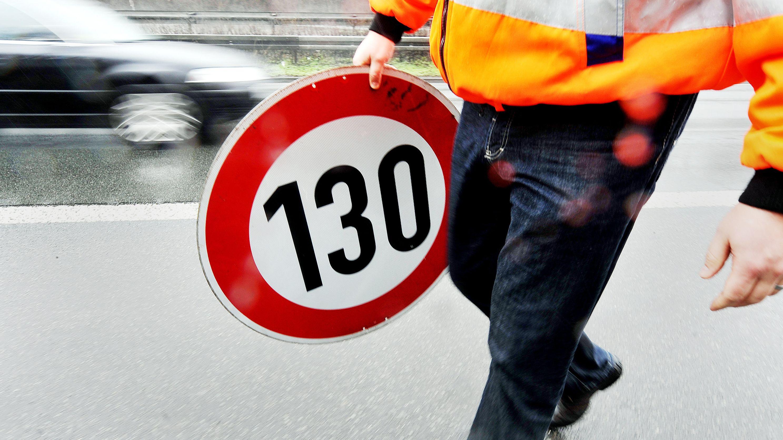 Ein Mitarbeiter einer Autobahnmeisterei trägt ein Schild zur Höchstgeschwindigkeit von 130 Stundenkilometern.