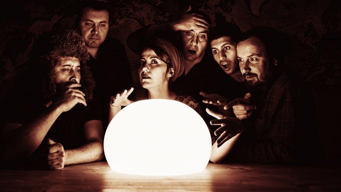 Sechs Personen (fünf Männer, eine Frau) sitzen um eine hell leuchtende Kugel herum
