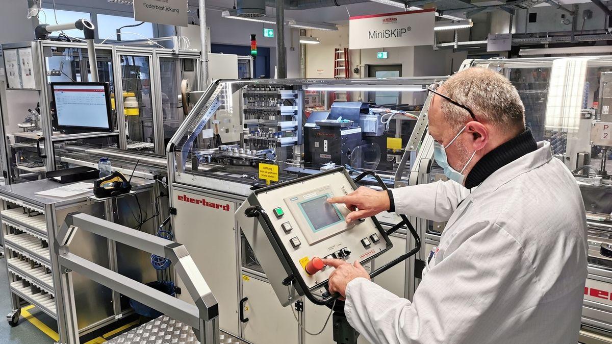 Ein Mann steht in einer Produktionshalle vor Maschinen.