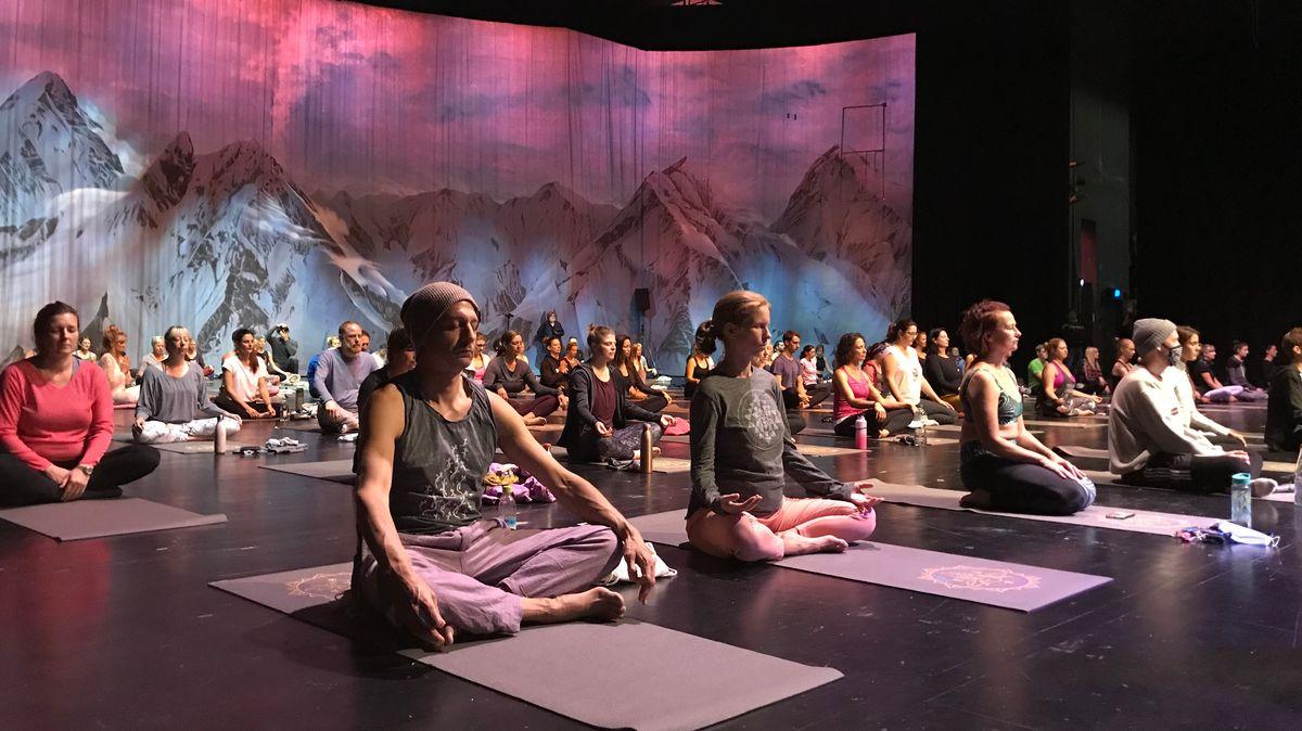 150 Menschen auf Yogamatten auf der Bühne des Festspielhauses Neuschwanstein. Im Hintergrund: Verschneite Alpenkulisse.