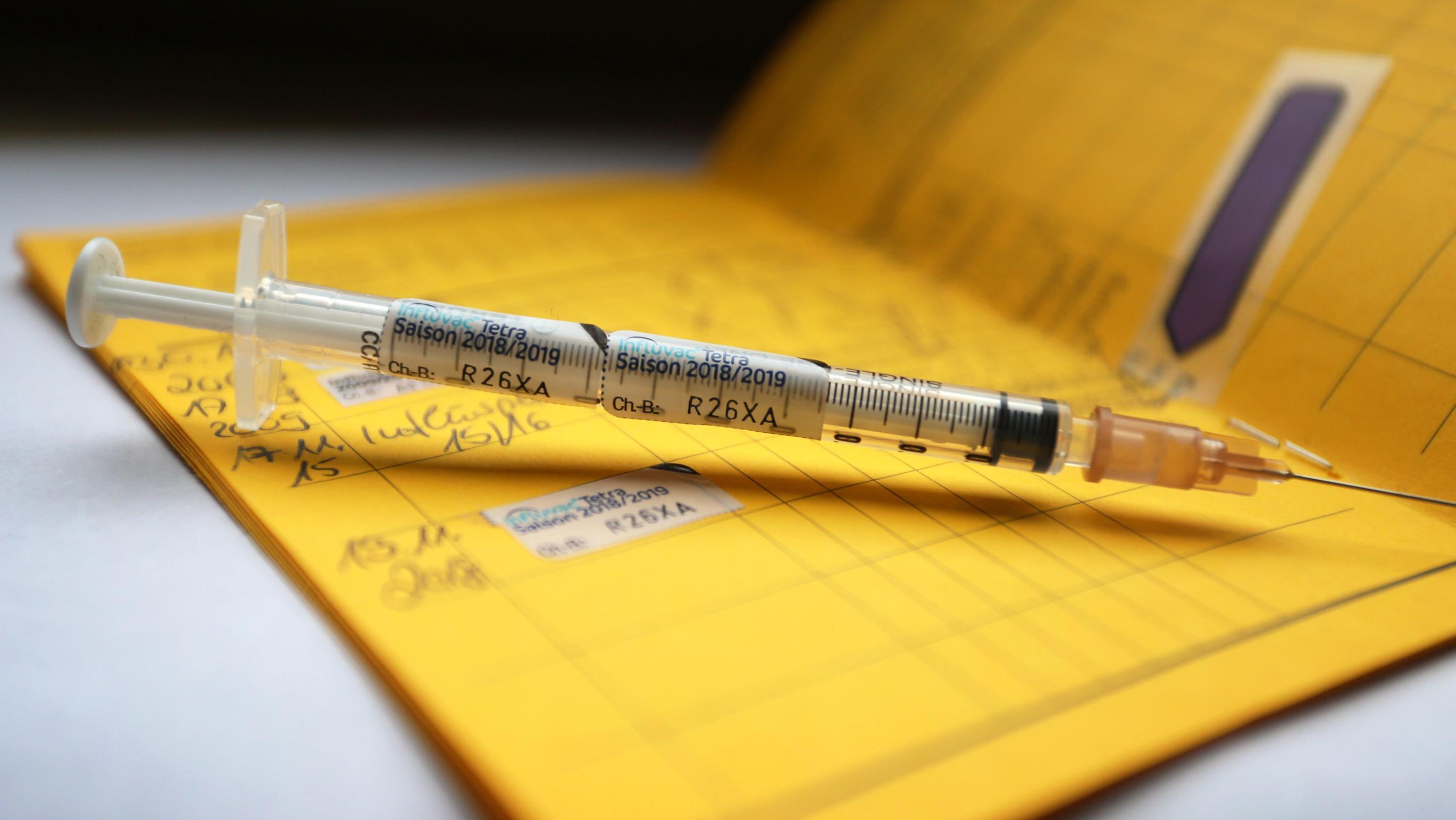 Eine Spritze, die mit dem Namen des Vierfach-Grippeimpfstoff Influvac Tetra gekennzeichnet ist, liegt auf einem Impfpass.