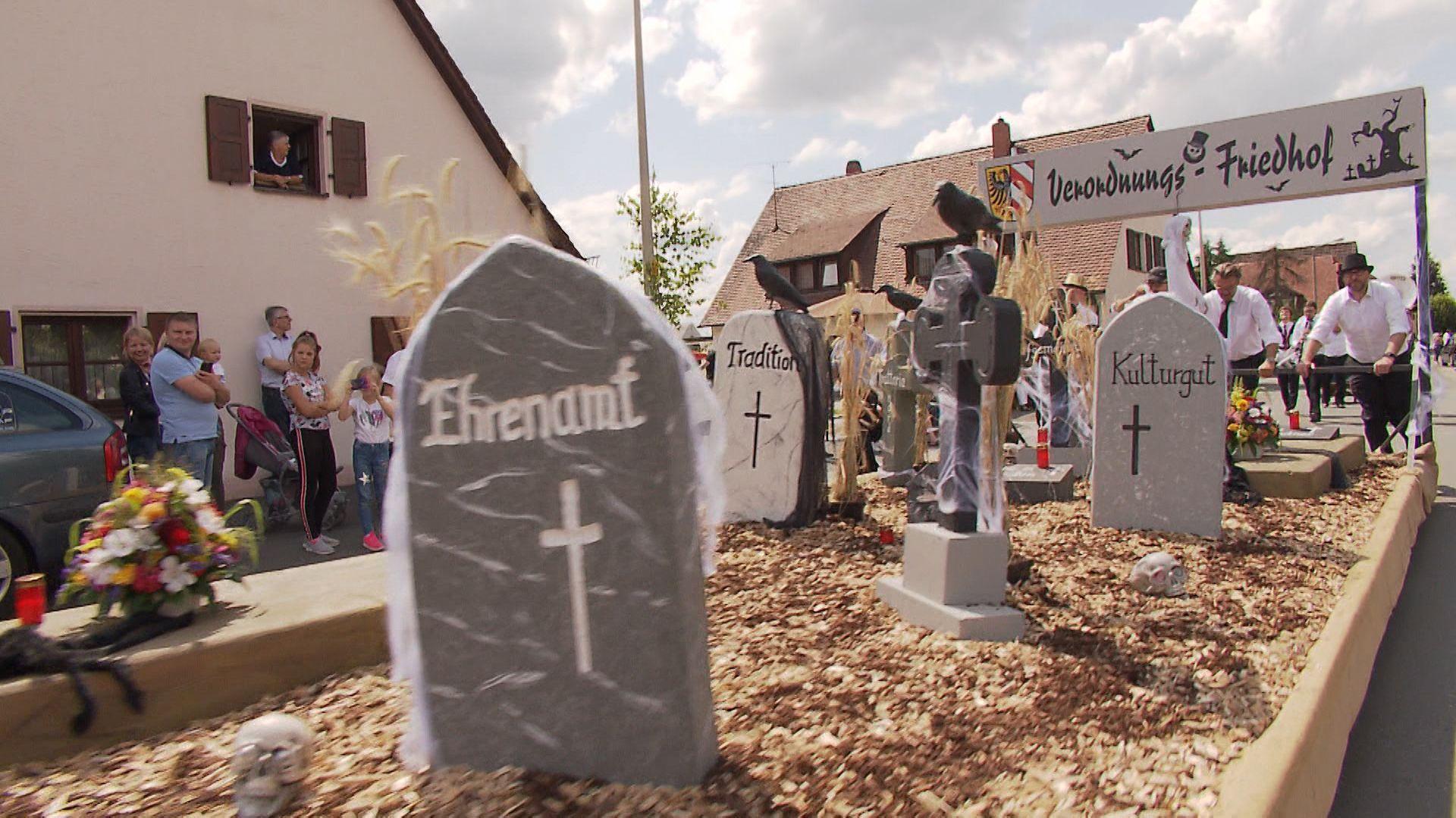 Rollender Friedhof mit Grabsteinen und Kreuzen fährt durch Almoshof