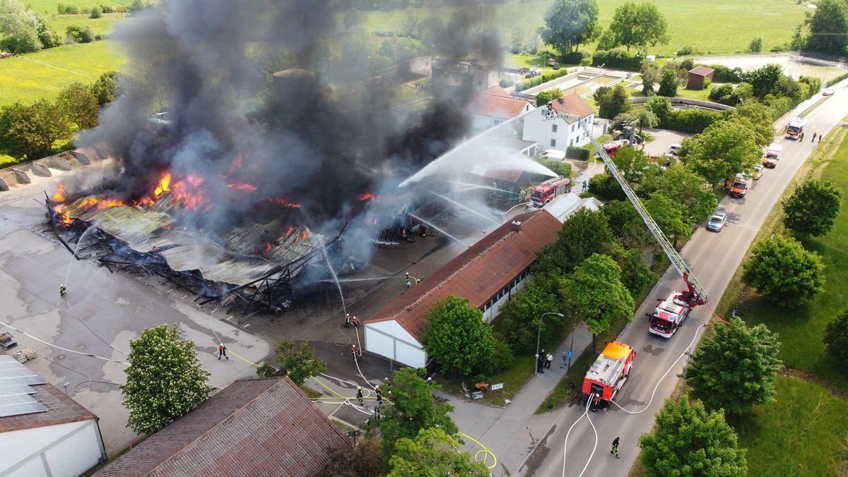 Lagerhallen stehen in Flammen, Feuerwehr löscht