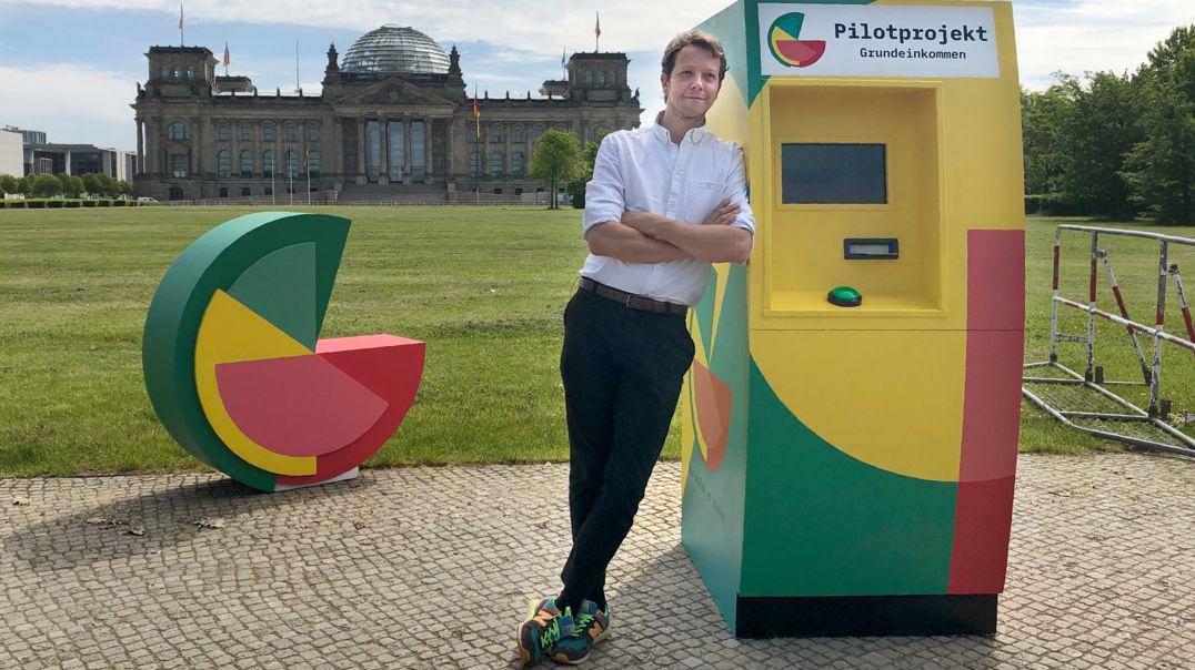 """Michael Bohmeyer, Initiator des Vereins """"Mein Grundeinkommen"""", steht an einem symbolischen Geldautomaten, im Hintergrund das Reichstagsgebäude."""