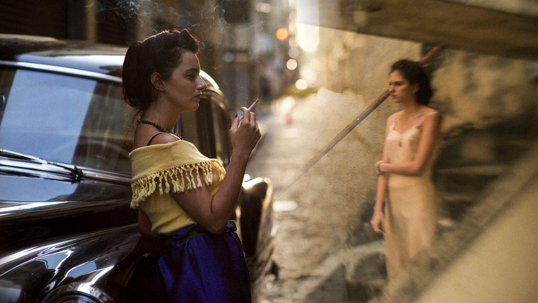 """Filmszene """"The Invisible Life of Eurídice Gusmao"""" von Karim Aïnouz (zwei junge Frauen stehen abends auf einer Straße, eine raucht)"""