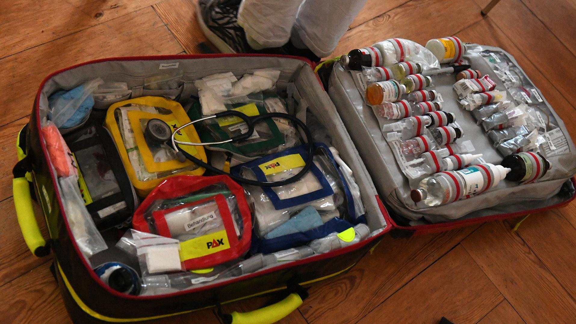Ein Notfallrucksack mit zahlreichen Medikamenten und Instrumenten liegt geöffnet auf dem Boden.