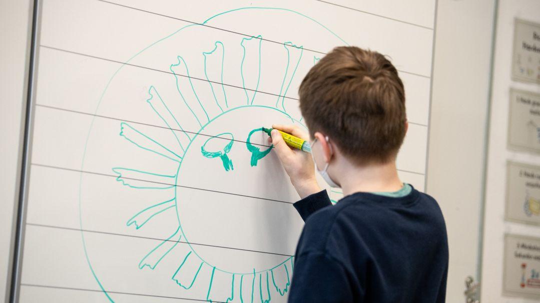 Ein Schulkind malt ein Corona-Virus