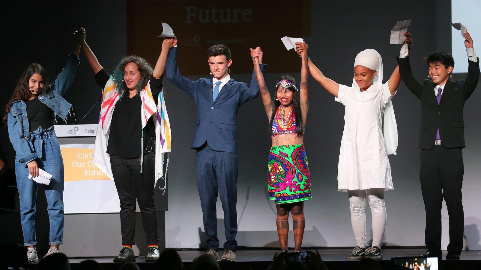 Junge Delegierte verschiedener Glaubensrichtungen stehen zum Auftakt der Konferenz in der Inselhalle auf der Bühne.