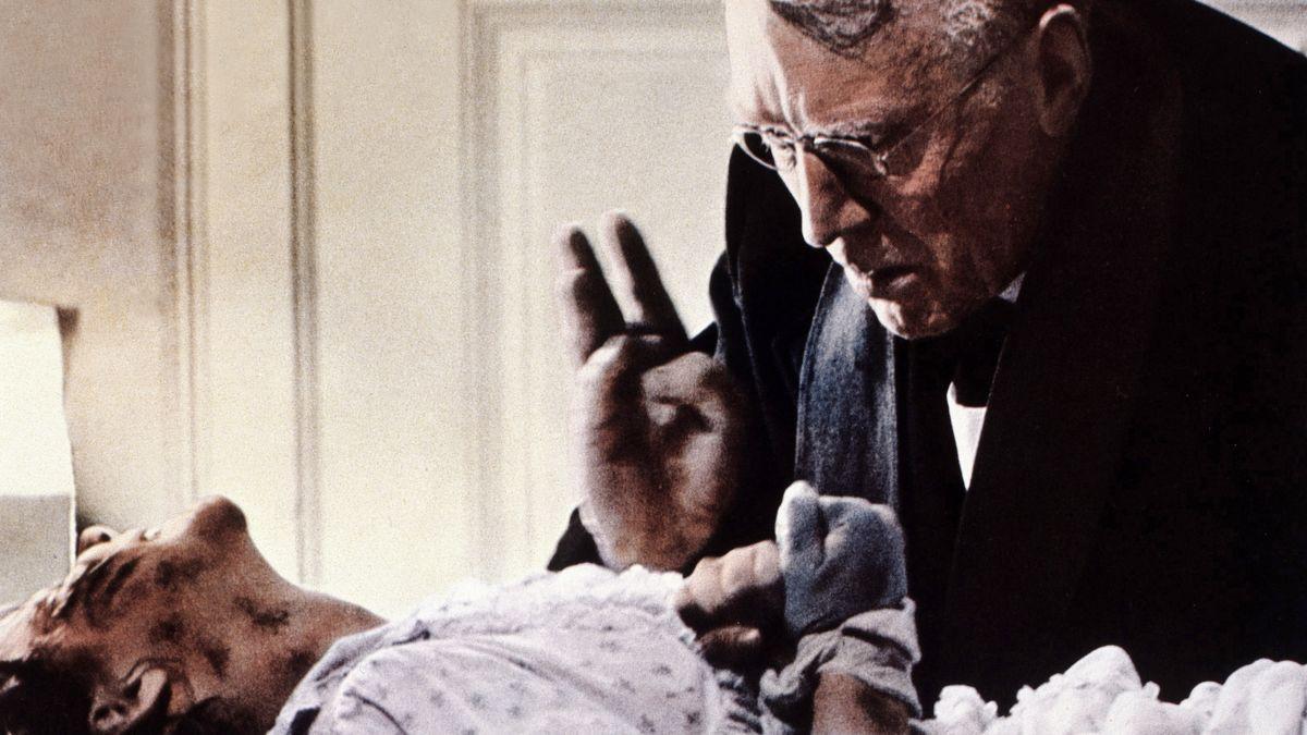 """Max von Sydow in """"Der Exorzist"""" (1973): Ein Priester sitzt am Bett eines krampfenden Mädchens und segnet es"""