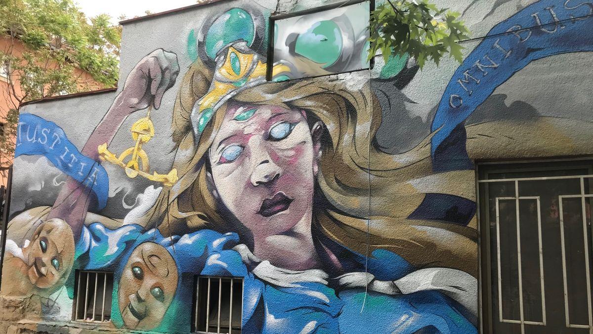 """Graffiti an einem Haus in Pristina, mit Schriftzug """"Justitia omnibus"""" und dem Kopf einer blinden Frau mit Waage"""