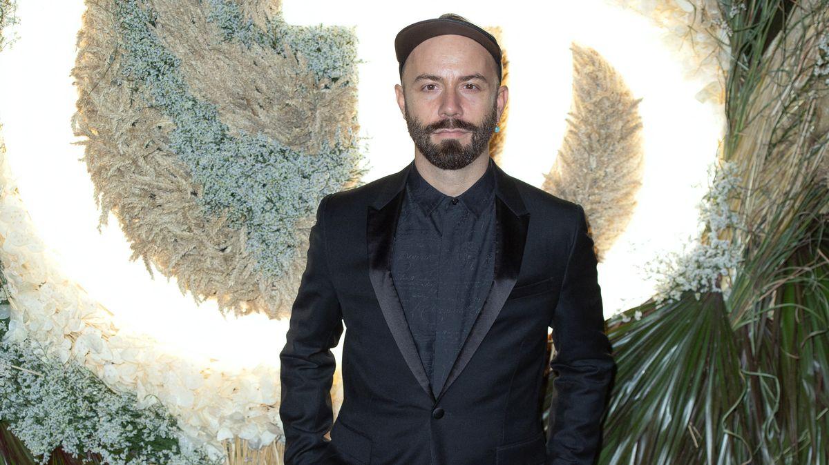 Yoann Lemoine aka Woodkid im Anzug mit Basecap vor einer opulenten Lampe mit pflanzenelementen.