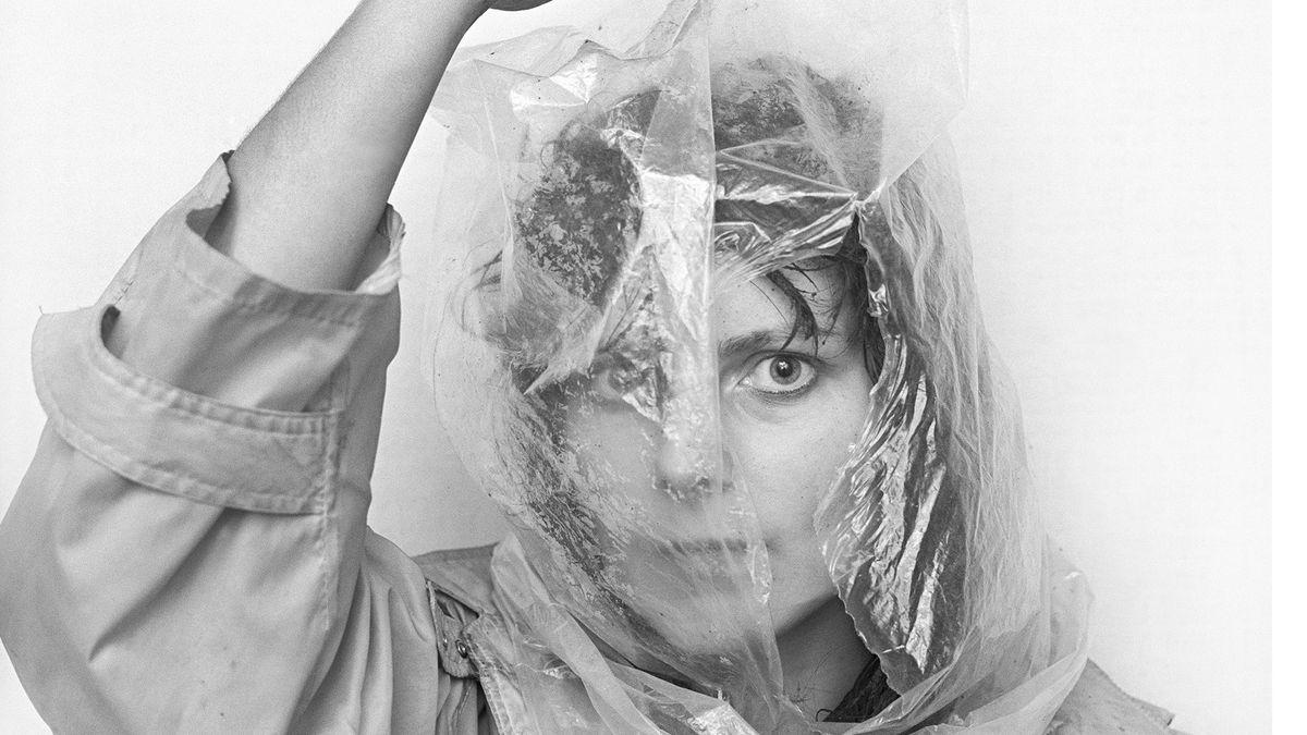 Schwarz-Weiß-Foto einer Frau die eine zerrissene Plastiktüte auf dem Kopf hat.