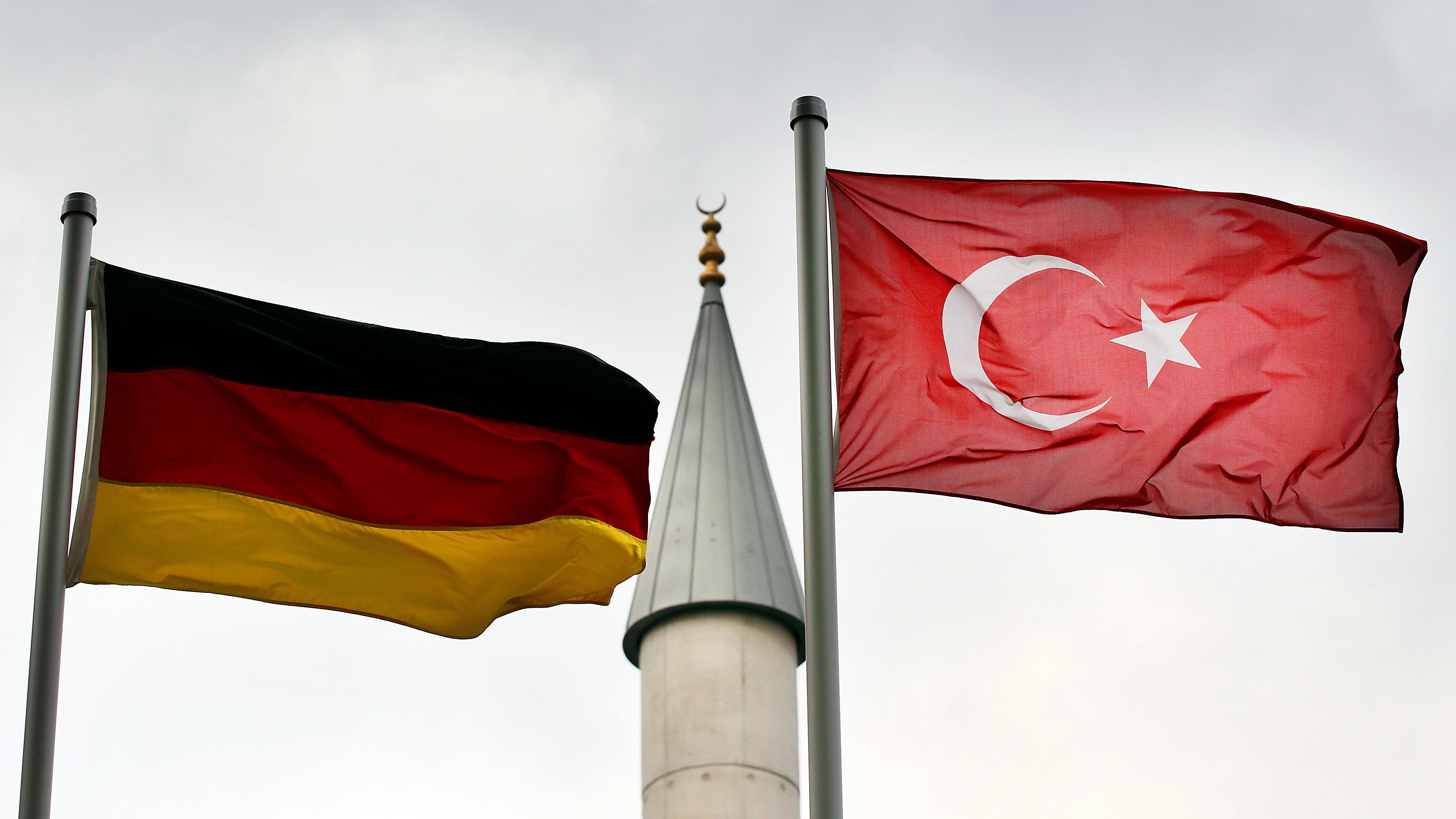 Eine deutsche und eine türkische Fahne wehen vor dem Minarett einer Moschee (Symbolbild).