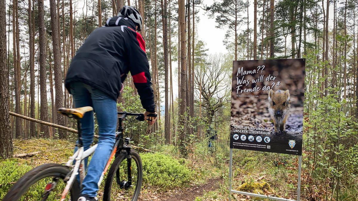 Mountainbiker fährt an einem Schild des BJV vorbei