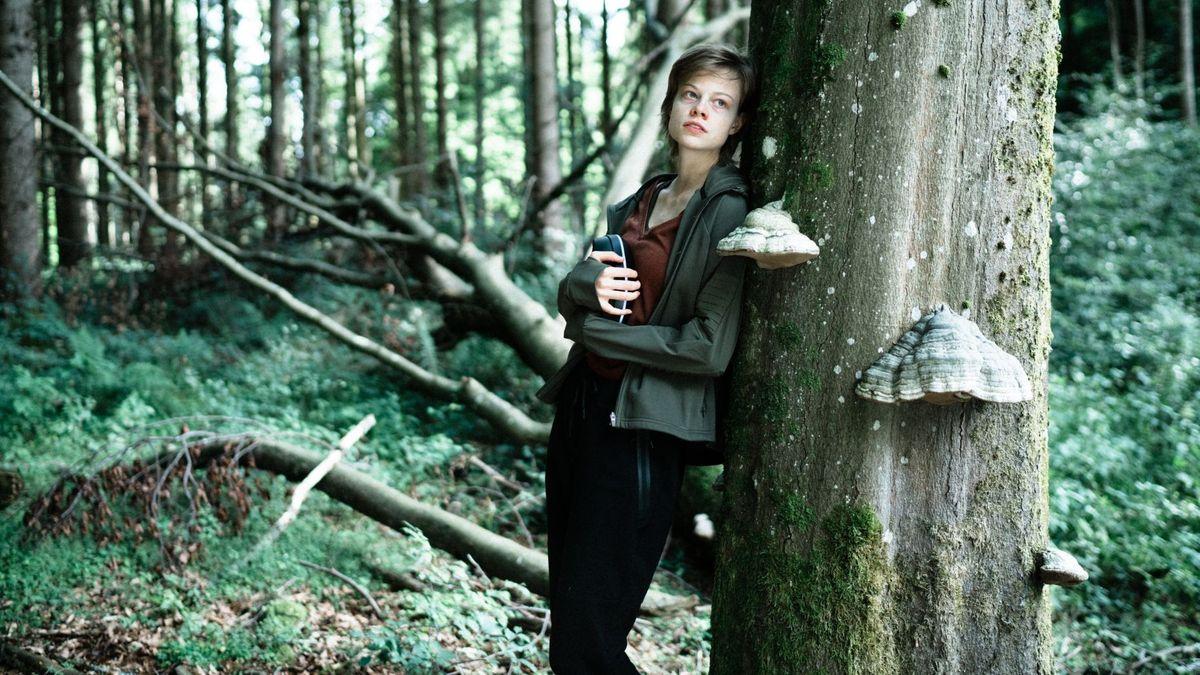 Die Schauspielerin im Wald mit einer Gaming-Brille in der Hand