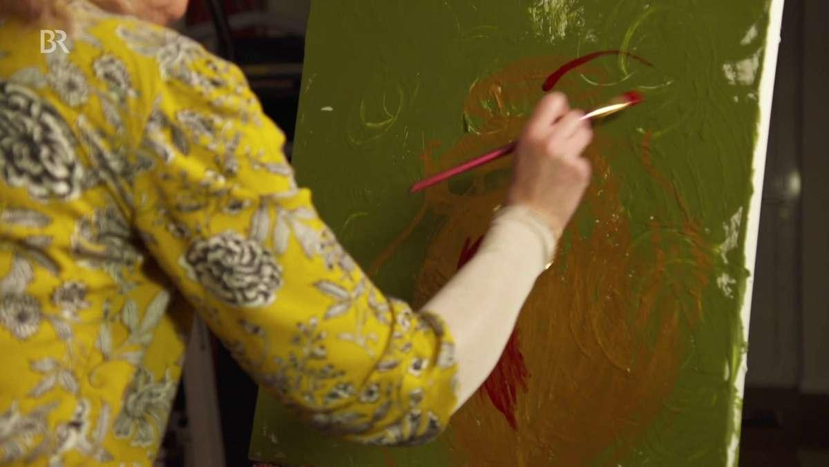 Die Künstlerin pinselt rote Farbe auf eine Leinwand. Darauf zu sehen: Grüner Hintergrund und eine goldene Vase.