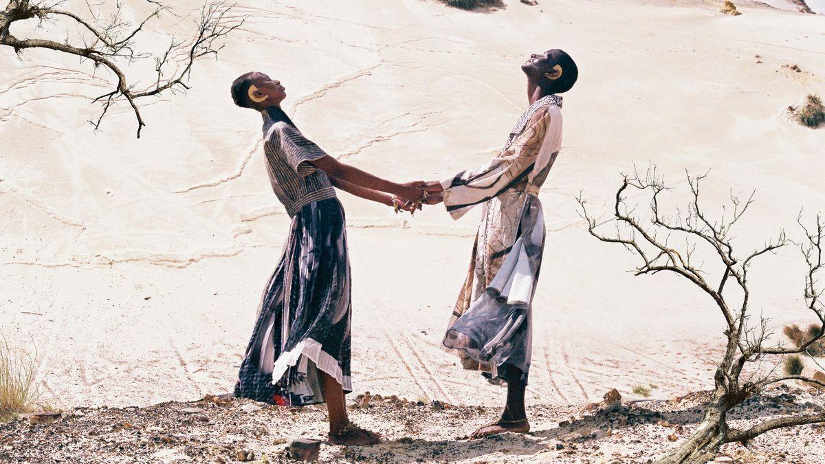Zwei Frauen stehen in der Steppe, halten sich an den Händen. Sie tragen weite, luftige Kleider und goldenen Ohrschmuck.
