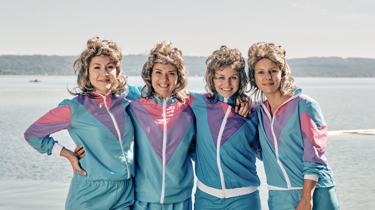 """Die vier Hauptdarstellerinnen der Serie """"Servus Baby"""" stehen nebeneinander, in türkis-glänzenden Trainingsanzügen, mit Vokuhila-Perücken vor Seekulisse"""