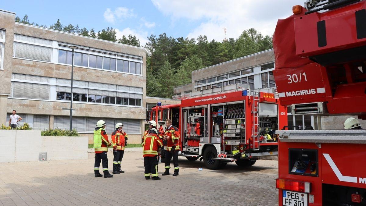 Feuerwehrleute und Feuerwehrautos stehen vor den Gebäuden der Realschule Pegnitz.