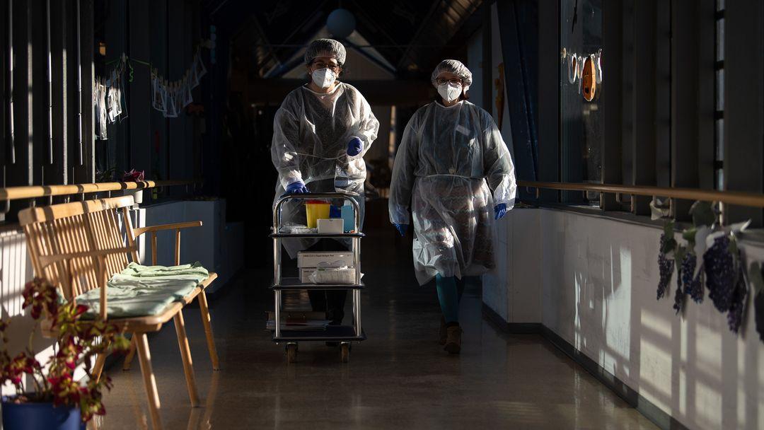 Zwei Altenpflegerinnen gehen in einem Tübinger Seniorenheim  mit Schutzausrüstung durch einen Gang.