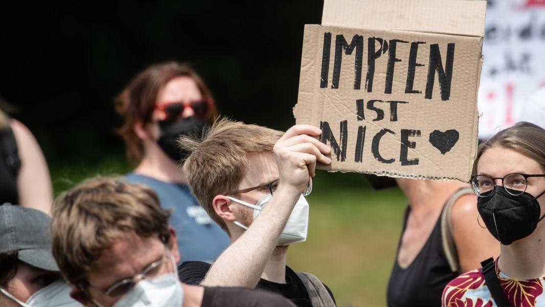 """03.06.2021, Baden-Württemberg, Karlsruhe: """"Impfen ist Nice"""" steht auf dem Schild eines Demonstranten, der an einer Gegendemonstration teilnimmt, die sich gegen die Demo der Initiative """"Querdenken"""" richtet."""