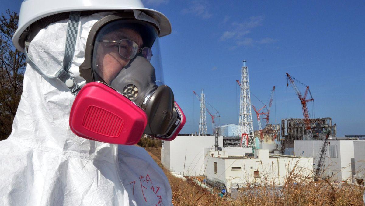 Besucher mit Atemmaske vor dem Atomkraftwerk Fukushima