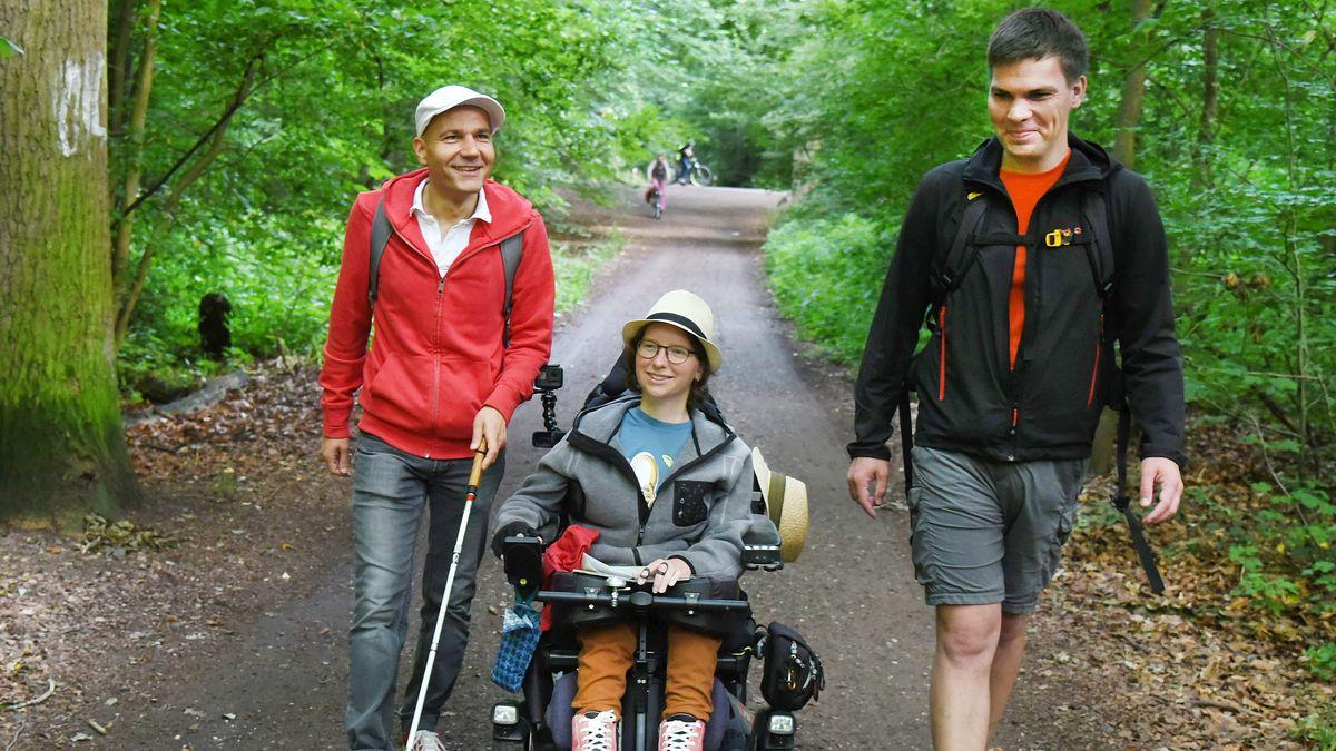 Ein sehbehinderter Mann (l.) und eine gehbehinderte Frau testen zusammen mit einem Begleiter (r.) die Barrierefreieheit eines Wanderwegs