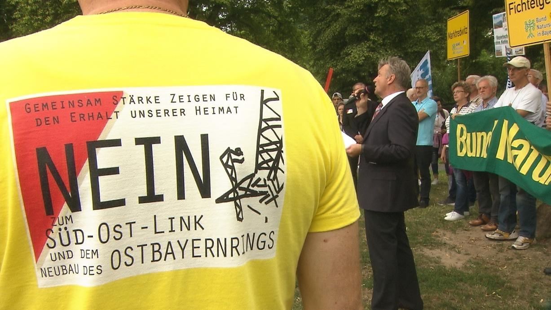 Auf dem Rücken eines gelben T-shirts ist die Aufschrift: Nein zum Süd-Ost-Link und dem Neubau des Ostbayernrings.
