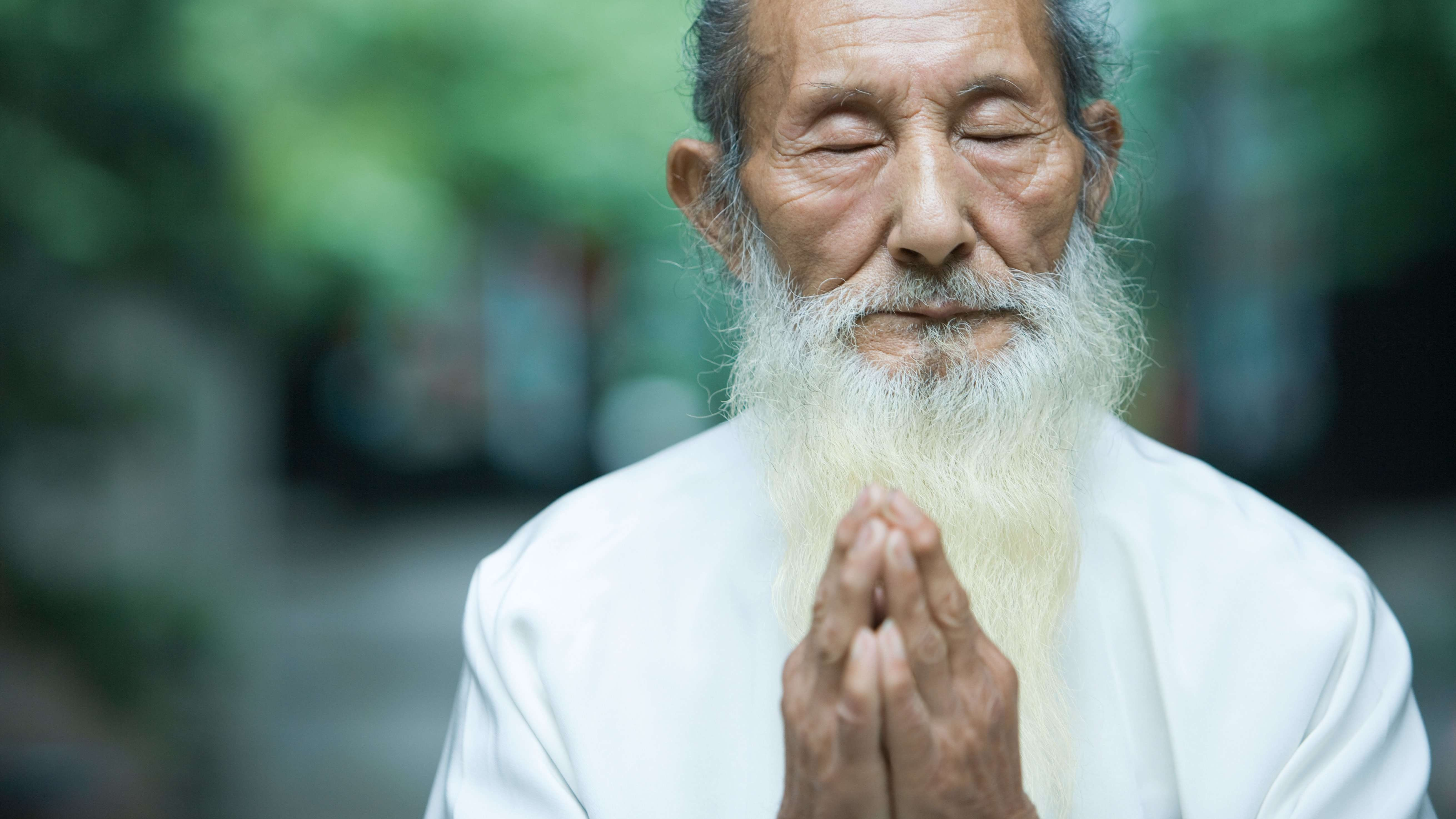 Alter Mann mit zum Gebet gefalteten Händen.