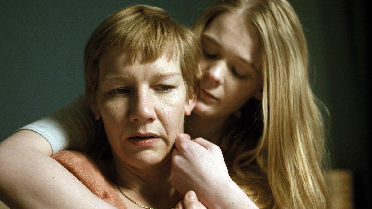 Eine Junge Frau umarmt von hinten eine ältere und redet ihr gut zu: Szene aus Schlaf