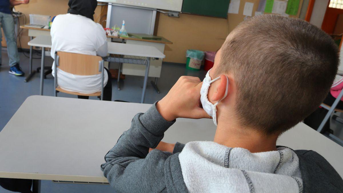 Schüler einer Mittelschule sitzen am ersten Schultag zu Beginn des Unterrichts mit Mundschutz im Klassenzimmer.