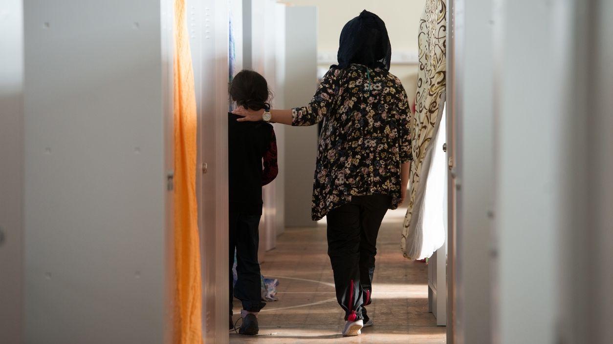 Frau mit Kind zwischen Metallschränken in einer bayerischen Flüchtlingsunterkunft